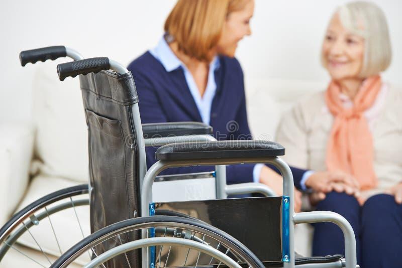 Oficio de enfermera casero para la mujer mayor con la silla de ruedas imagen de archivo libre de regalías