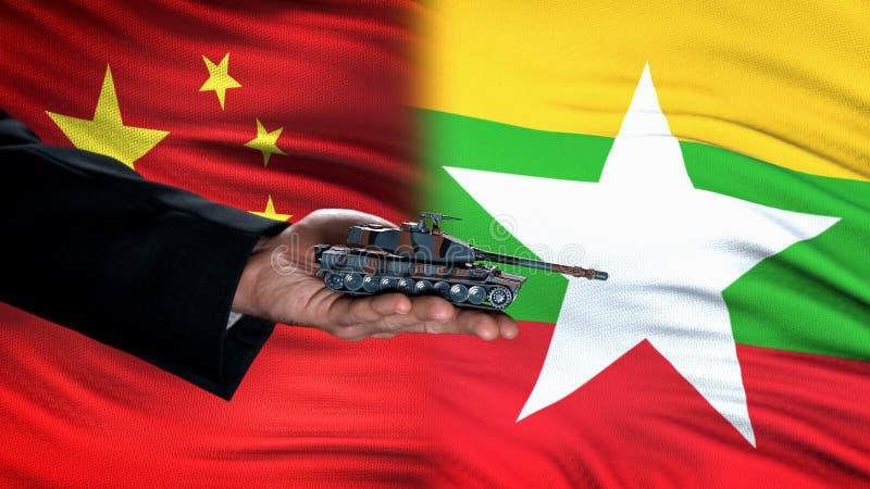 Oficjalne trzymanie zbiornika na zabawki na tle Chin i flagi Myanmar, handel fotografia stock