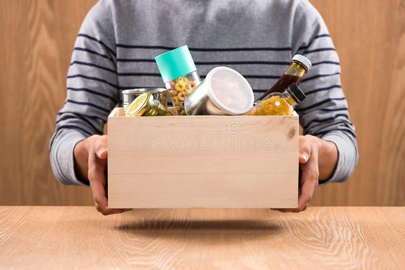 Ofrézcase voluntariamente con la caja de la donación con los productos alimenticios en fondo de madera imagenes de archivo