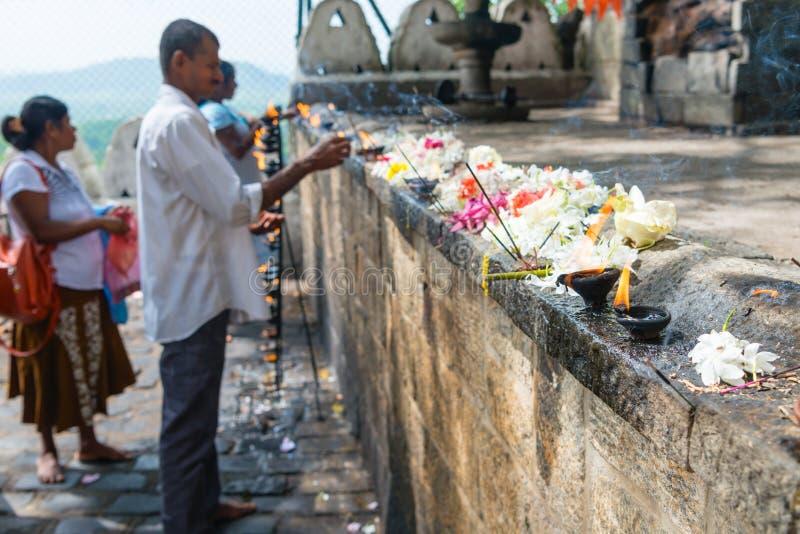 Ofrendas del lugar de la gente con los palillos fragantes, las flores frescas y b imagenes de archivo