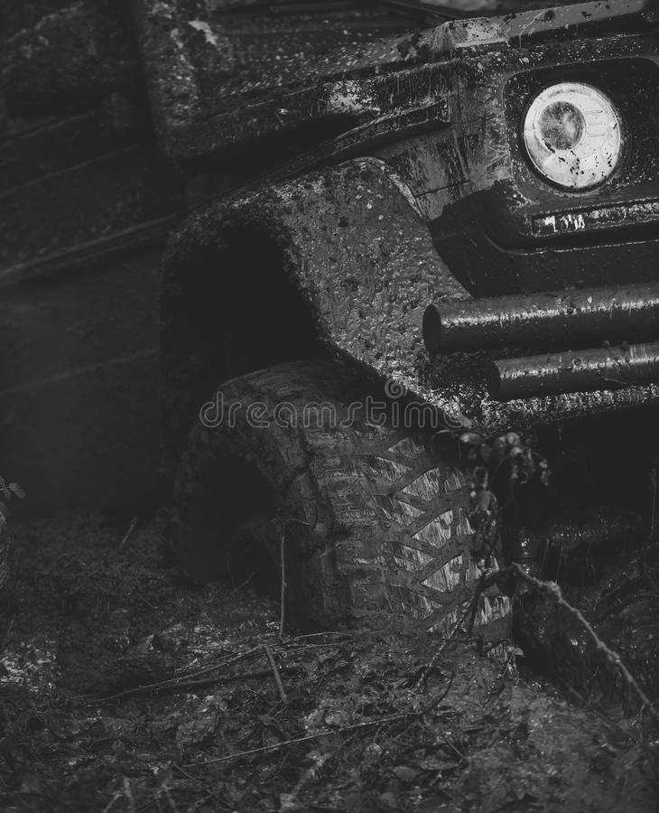 Ofroad for hard man. Extreme entertainment concept. Offroad tire covered with mud. Overcomes obstacles on nature background. Fragment of car stuck in dirt stock photography
