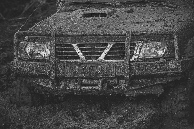Ofroad for hard man. Part of offroad car stuck in mud on dark background. stock photo