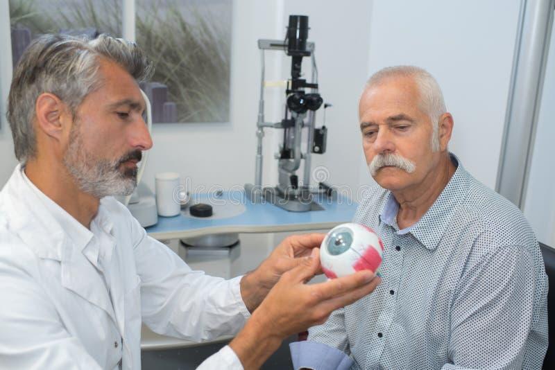 Oftalmólogo con el paciente modelo del mayor de la demostración del ojo foto de archivo libre de regalías