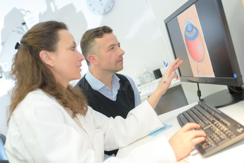 Oftalmólogo que muestra el ojo paciente de la imagen en la PC imágenes de archivo libres de regalías