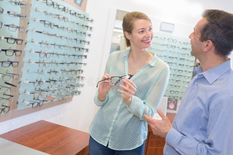 Oftalmolog i kobieta wybiera szkła przy optyka sklepem obraz stock