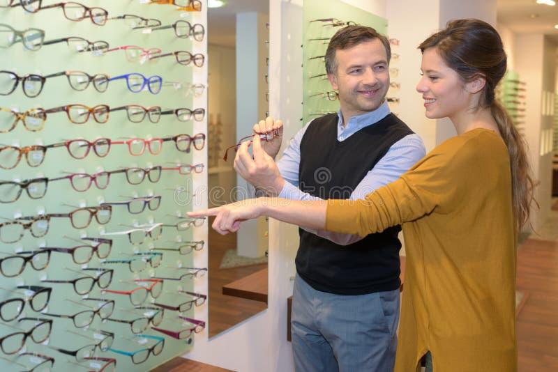 Oftalmolog i piękna brunetki kobieta wybiera szkła w optyka sklepie zdjęcia stock