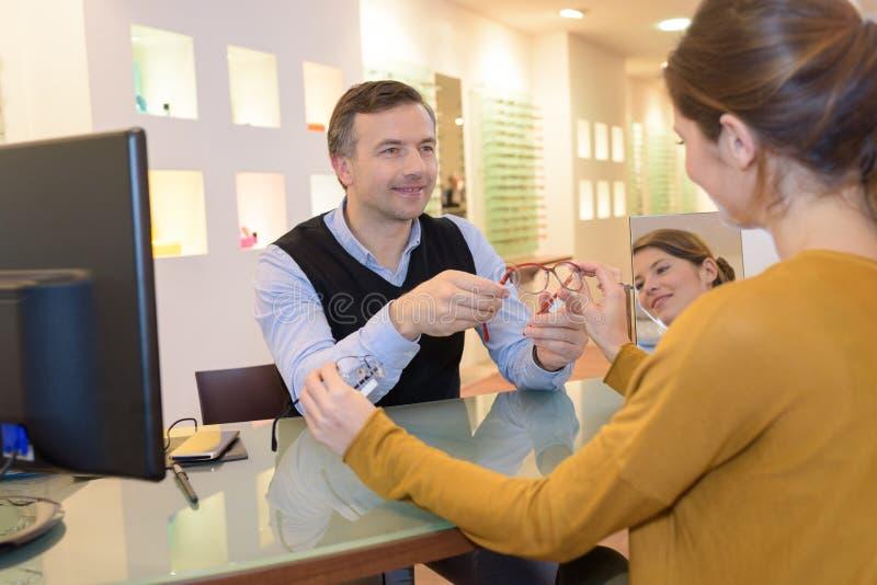 Oftalmolog i piękna brunetki kobieta wybiera szkła w optyka sklepie obraz stock