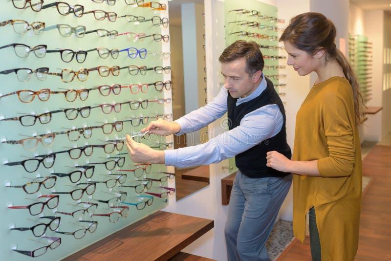 Oftalmolog i piękna brunetki kobieta wybiera szkła w optyka sklepie fotografia stock