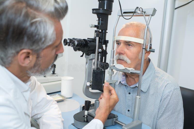 Oftalmolog robi oko testowi na starym pacjencie zdjęcia stock