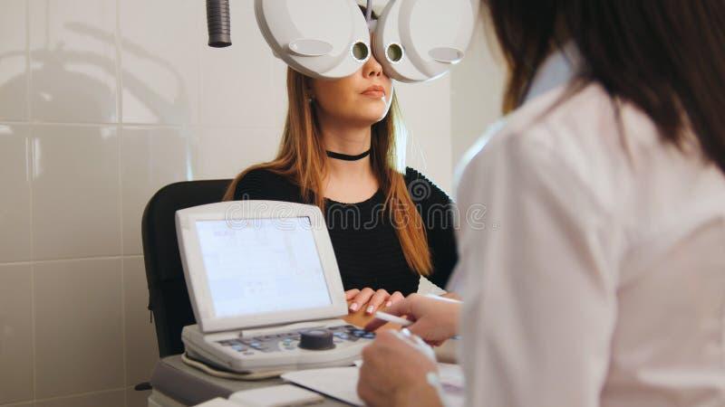 Oftalmologi - begrepp för ögonklinik - optometriker och patient som gör examenvision royaltyfria foton