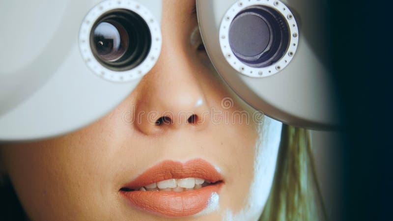 Oftalmologi - den unga kvinnan kontrollerar ögonen på den moderna utrustningen i vårdcentralen arkivbild