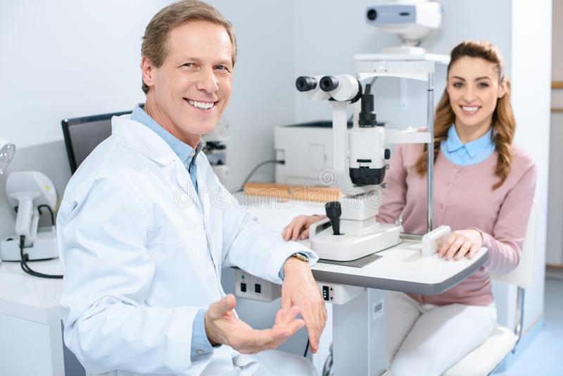 oftalmologista e paciente de sorriso perto da lâmpada cortada foto de stock royalty free