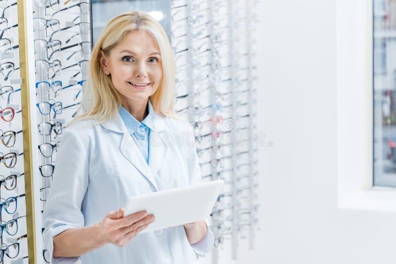 oftalmologista fêmea profissional que trabalha com a tabuleta no sistema ótico com vidros imagem de stock