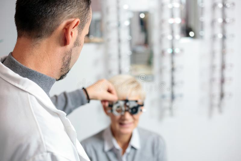 Oftalmologista masculino que examina a mulher madura na clínica da oftalmologia, determinando o diopter imagens de stock