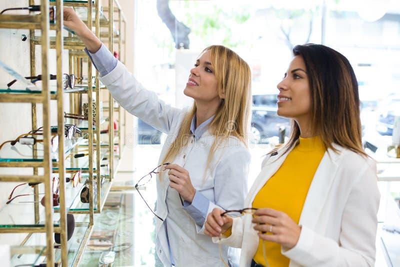 Oftalmologista novo atrativo que mostra monóculos à jovem mulher bonita na loja ótica fotografia de stock