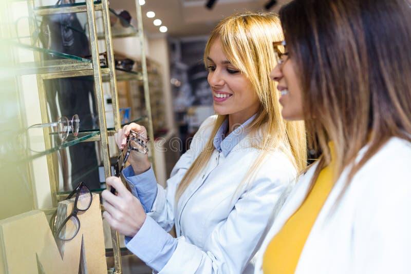 Oftalmologista novo atrativo que mostra monóculos à jovem mulher bonita na loja ótica fotografia de stock royalty free