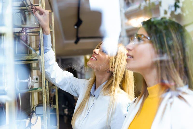 Oftalmologista novo atrativo que mostra monóculos à jovem mulher bonita na loja ótica imagens de stock royalty free