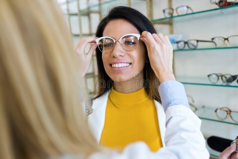 Oftalmologista novo que põe sobre monóculos na mulher bonita de sorriso na loja ótica imagem de stock royalty free