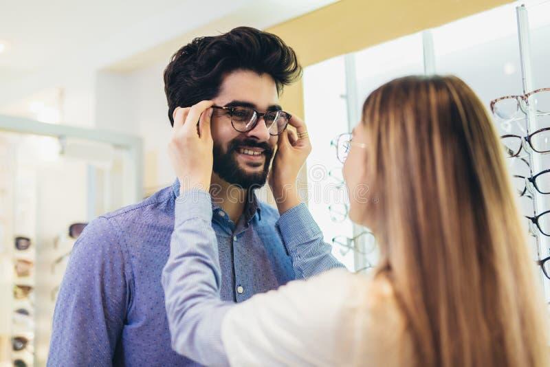 Oftalmologista que ajuda o homem a escolher óculos em loja ótica fotografia de stock