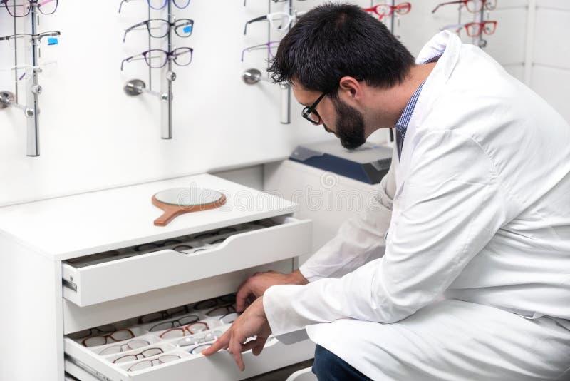oftalmologista que escolhe vidros de uma gaveta na loja ótica imagem de stock royalty free