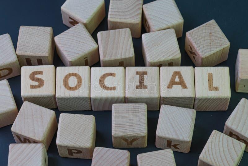 Ogólnospołeczni środki lub ludzki społeczności pojęcie, sześcianu drewniany blok z abecadło syndykatem słowo socjalny na czarnym  zdjęcia stock