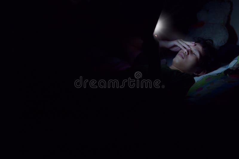 Ogólnospołeczni środki uzależniają się po obracać daleko światło ciemnego pokój, mężczyzna na łóżko nie sen ponieważ sztuka mądrz zdjęcie royalty free