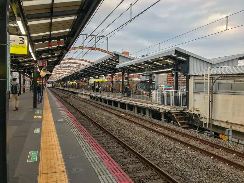 Ogólny widok dojeżdżający czekać na ich następnego pociąg w wczesnym poranku mży przy Osaka dworcem po tym jak drobny zdjęcie royalty free