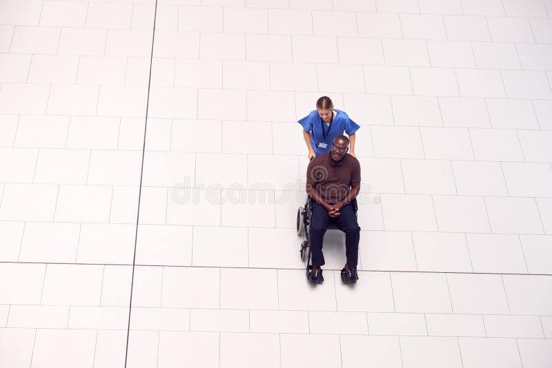 Ogólny Widok Na Pielęgniarkę Kojarzącą Pacjenta Na Wózku Przez Lobby Nowoczesnego Budynku Szpitalnego obraz stock