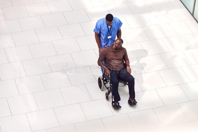 Ogólny Widok Pielęgniarki Na Wózkach Przez Lobby Nowoczesnego Budynku Szpitalnego zdjęcia royalty free