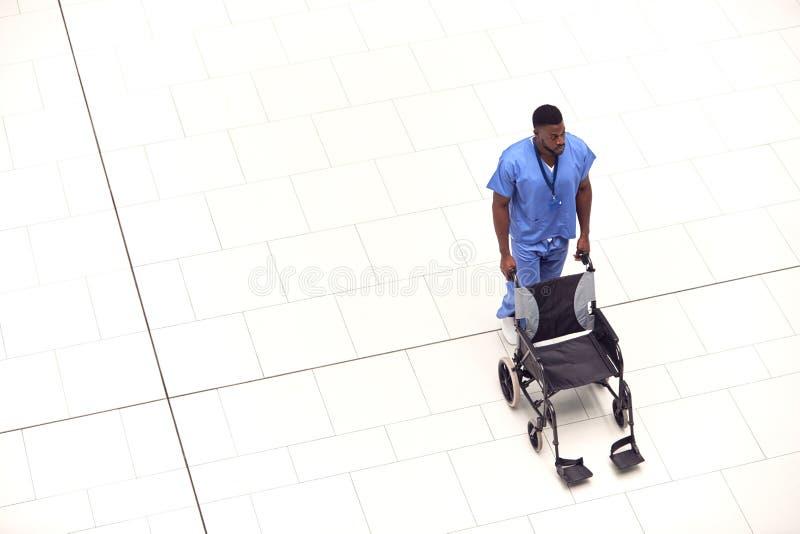 Ogólny Widok Pielęgniarki Pchającej Puste Wózek Przez Lobby Nowoczesnego Budynku Szpitalnego obrazy stock