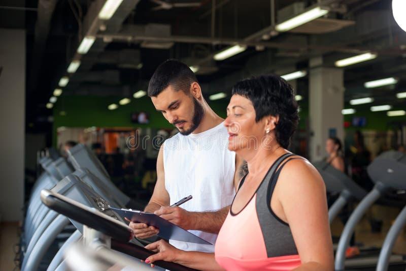 Ogłoszenie towarzyskie trener z w średnim wieku kobietą w gym zdjęcie royalty free