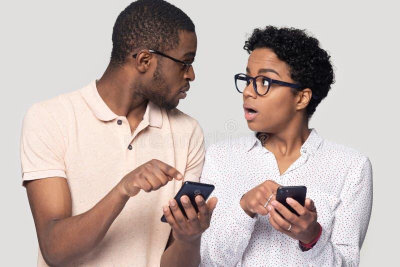 Ogłuszona etniczna para zaskakiwał dostawać wiadomość na smartphones fotografia royalty free