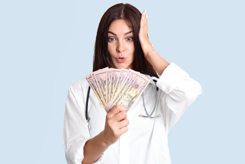 Ogłuszony żeński lekarz z ciemnym włosy, spojrzenia przy dolarami zaskakująco, otrzymywa ogromny bribary, zaangażowany w korupci, zdjęcie royalty free