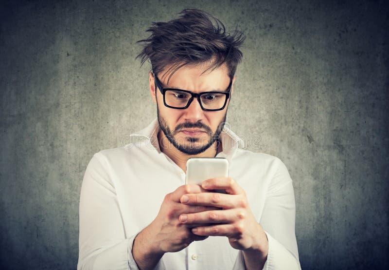 Ogłuszony mężczyzna, zdziwiony obrażać, co widzii na jego smartphone fotografia royalty free