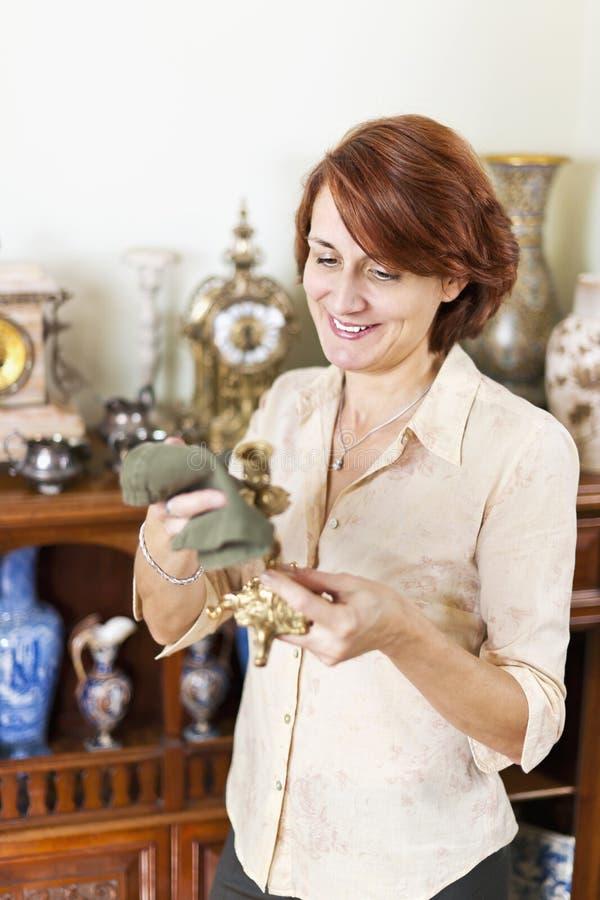 Oggetti d'antiquariato di lucidatura della donna immagine stock