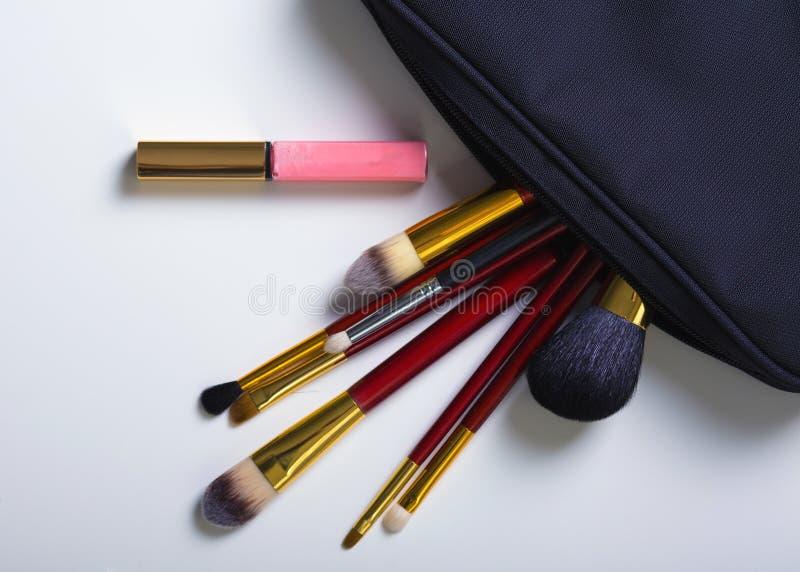 Oggetti della donna di modo Componga la borsa con i cosmetici su fondo bianco disposizione del fkat, vista superiore immagini stock
