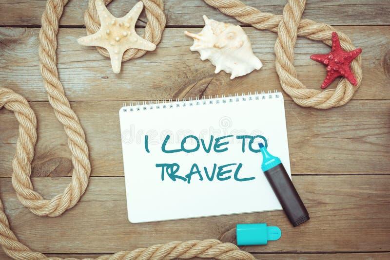 Oggetti e testo marini in blocco note: Amo viaggiare immagine stock libera da diritti