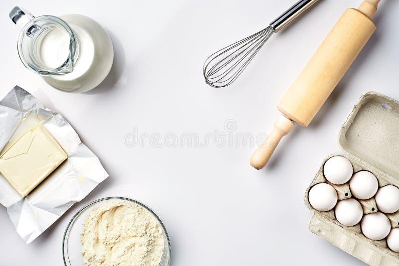 Oggetti ed ingredienti per cuocere, muffe della plastica per i biscotti su un fondo bianco La farina, uova, matterello, sbatte fotografia stock libera da diritti