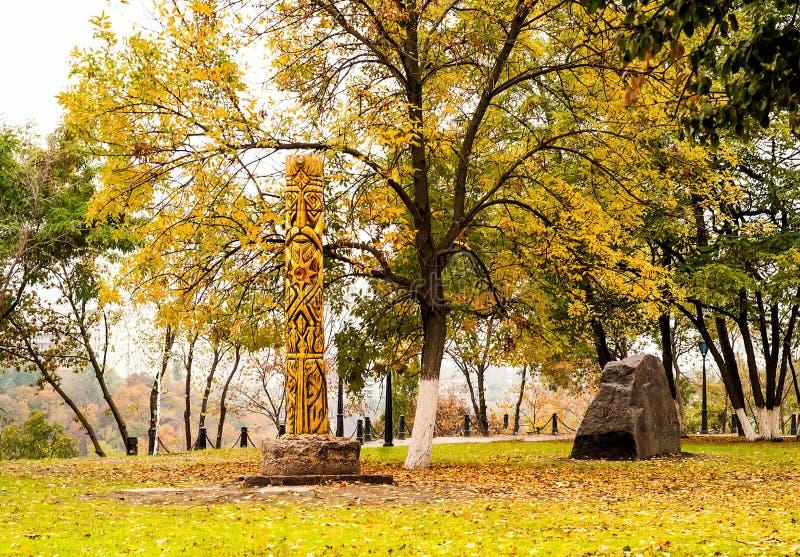 Oggetti magici antichi, idolo di legno, dio pagano sui precedenti del paesaggio urbano di autunno, luce naturale, fine su immagine stock libera da diritti