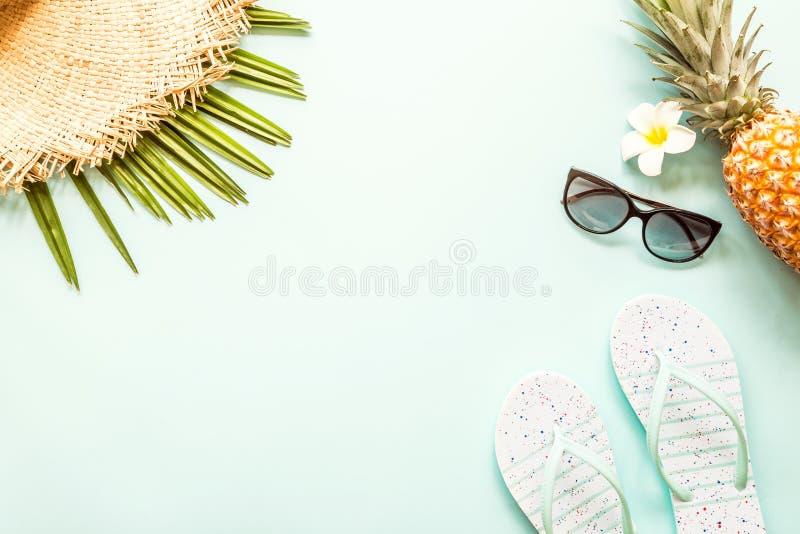 Oggetti posti piani di viaggio: ananas, cappello di paglia, fiore, occhiali da sole, pantofole della spiaggia e foglia di palma f fotografia stock