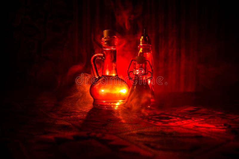 Oggetto d'antiquariato e bottiglia di vetro d'annata su fondo nebbioso scuro con luce Veleno o concetto del liquido di magia fotografia stock