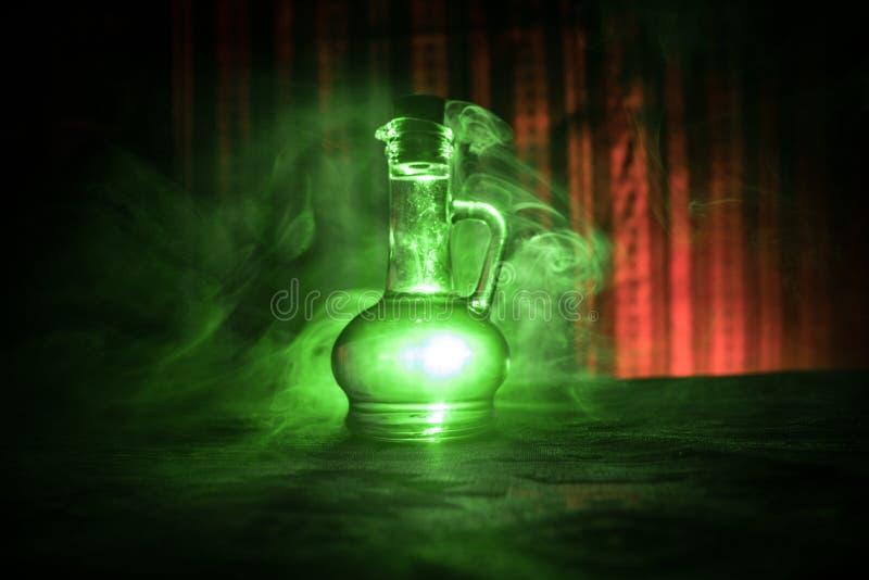 Oggetto d'antiquariato e bottiglie di vetro d'annata su fondo nebbioso scuro con luce Veleno o concetto del liquido di magia fotografia stock