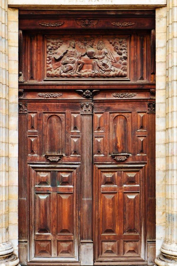 Oggetto d'antiquariato e doppia porta di legno decorata di vecchia chiesa con sollievo religioso fotografia stock
