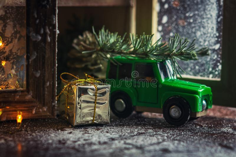 Oggetto dorato della decorazione del contenitore e di natale di regalo con l'automobile verde del giocattolo che porta un albero  immagine stock libera da diritti
