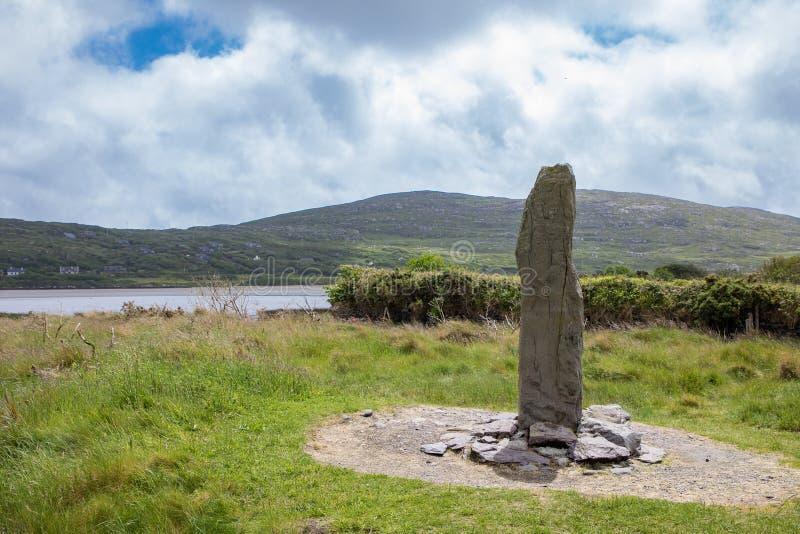 Ogham sten i irländskt landskap under molnig blå himmel royaltyfria foton