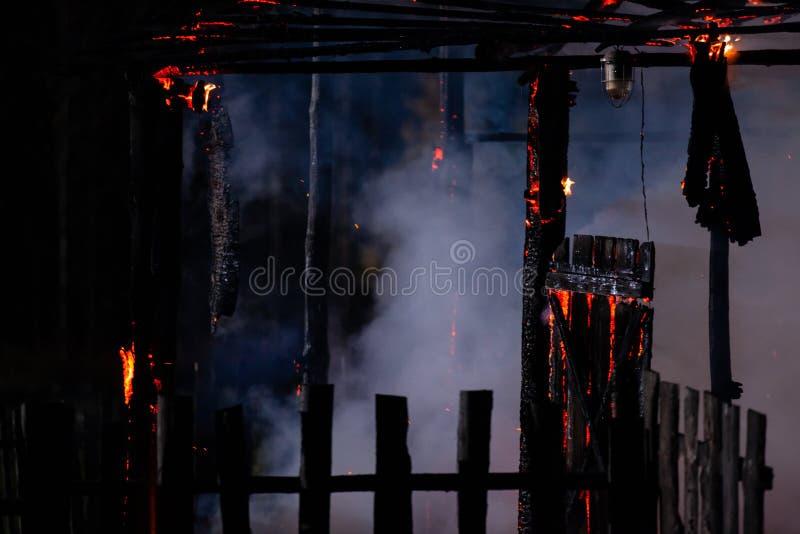 Ogień w nocy Zniszczony wiejski dom i płot fotografia royalty free