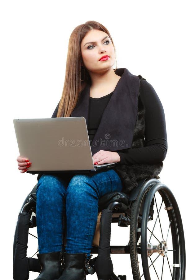 Ogiltig flicka för kvinna på rullstolen genom att använda datoren fotografering för bildbyråer