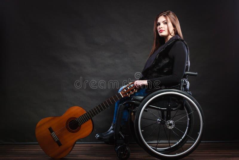 Ogiltig flicka för kvinna på rullstolen med gitarren royaltyfri bild