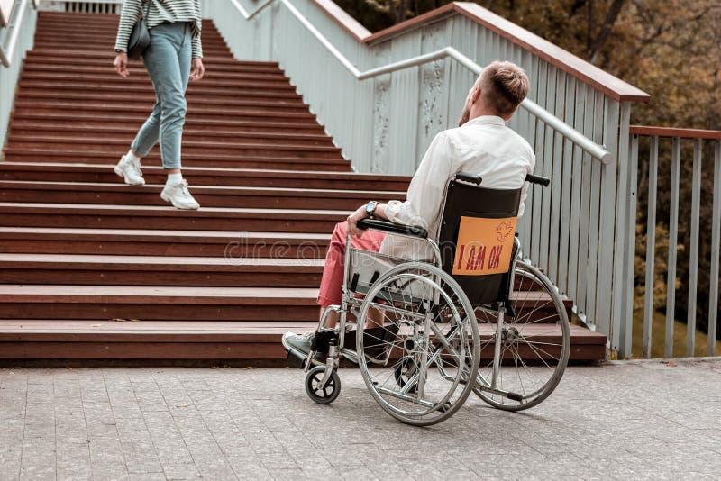 Ogiltigt mansammanträde i rullstolen och se trappan arkivbilder