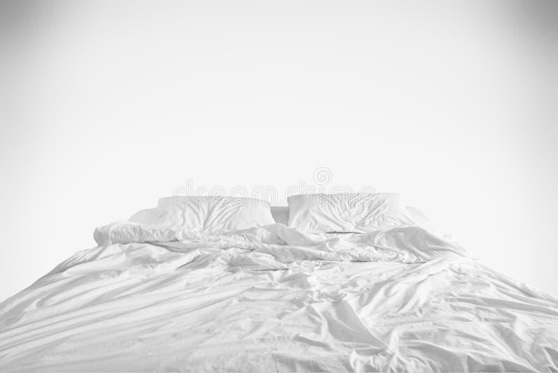 Ogjord säng med det skrynkliga sängarket, en filt och kuddar efter komfortduntäcke sover att vakna upp i morgonen på vit arkivbilder